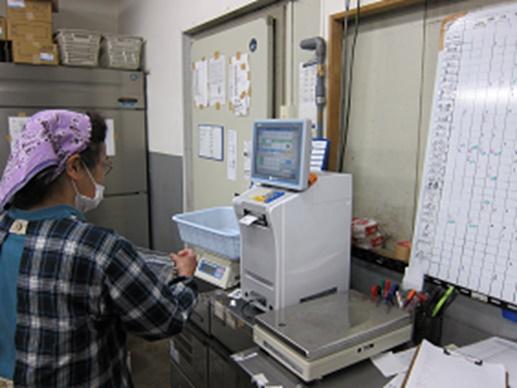 計量器(はかり)を利用してパックした商品を一つずつ計量し商品をバーコード化します。1グラム単位で測定して店舗への請求データと紐づけています
